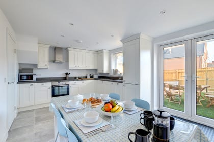 Bright kitchen/diner with patio doors leading to garden