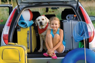dog in car with girl with suitcases