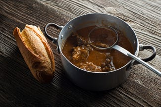 Metal pan with meat stew and a half baguette of bread