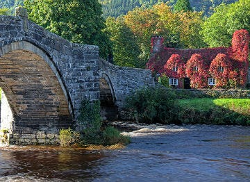 Ivy clad cottage on a river with bridge at Llanrwst