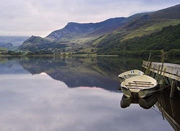 Boats on a still lake surrounded by Welsh mountains