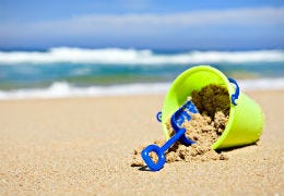 Green bucket and blue spade on a beautiful sandy beach with blue sea in the background